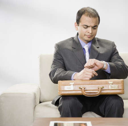 Indian businessman with briefcase looking at watch Stock Photo - 16092387