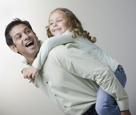 fathering: Hispanic father giving daughter piggyback ride