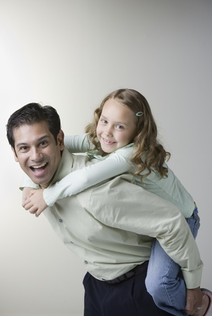 Hispanic father giving daughter piggyback ride Stock Photo - 16092408