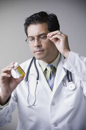 Hispanic male doctor looking at medication bottle