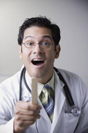 Hispanic male doctor holding tongue depressor