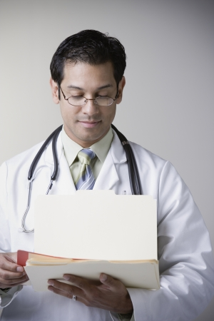 Hispanic male doctor reading file