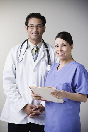 Portrait of Hispanic male doctor and nurse holding file Stock Photo - 16092414