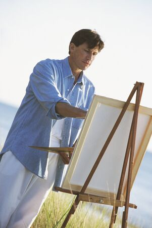 Man painting on easel outdoors