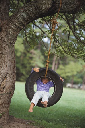 Young girl sitting in tire swing