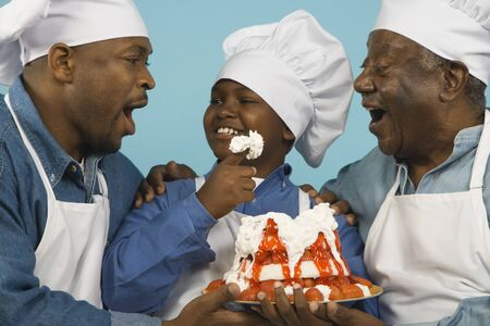 Multi-generational African male family members in chef's hats with cake Stock Photo - 16092436