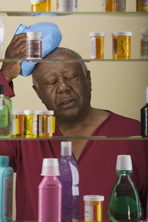1 person: Sick senior African man in front of medicine cabinet LANG_EVOIMAGES