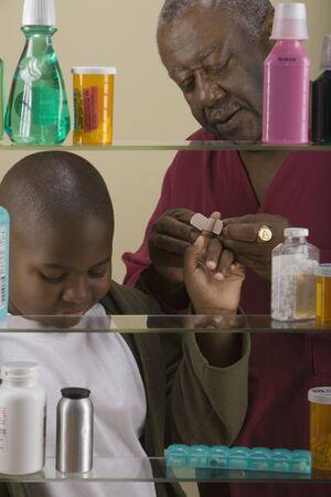 harming: African grandfather bandaging grandson's finger in front of medicine cabinet