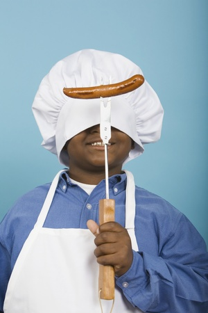 attired: African boy in chef's hat holding hot dog LANG_EVOIMAGES