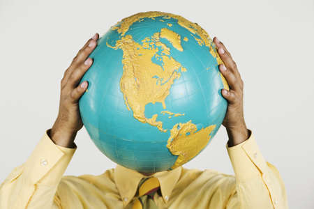 Native American businessman holding globe in front of face Stock Photo - 16092444