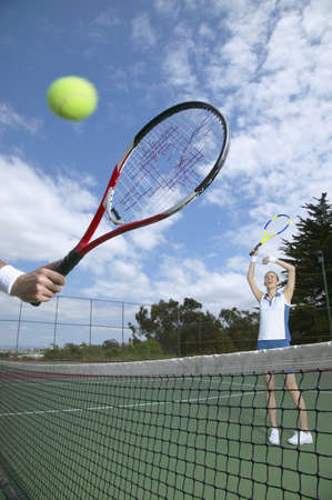 lower section view: Woman hitting tennis ball through other players racket
