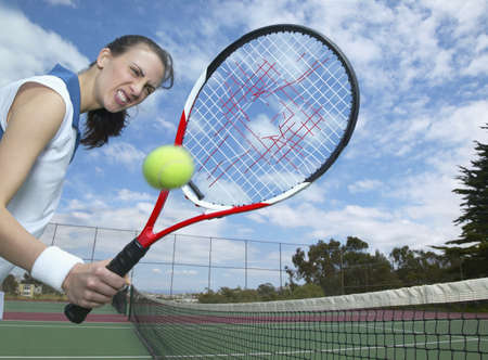 Hispanic woman holding tennis racket with hole in it Stock Photo - 16092447