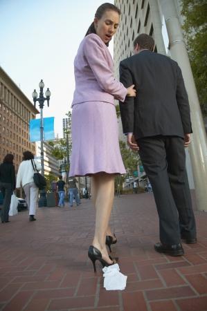 shaming: Hispanic woman noticing toilet paper on shoe outdoors