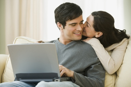 Hispanic couple hugging and using laptop Stock Photo - 16092454