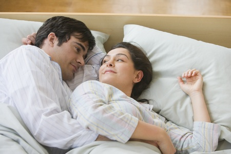 Hispanic couple smiling at each other in bed