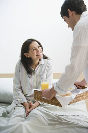 Hispanic man bringing breakfast to wife in bed Stock Photo - 16092456