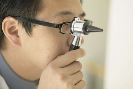 exactitude: Asian male doctor looking through medical instrument