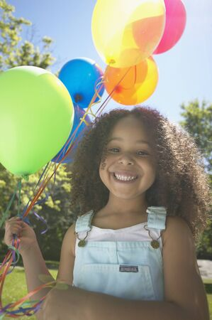 Close up of African girl holding balloons