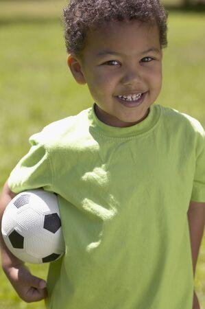 relishing: African boy holding soccer ball