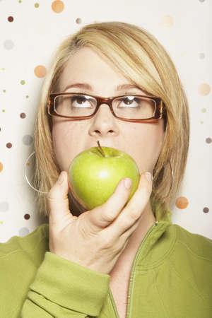 tiring: Young woman eating apple