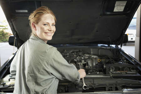 bonnet up: Female auto mechanic working on car