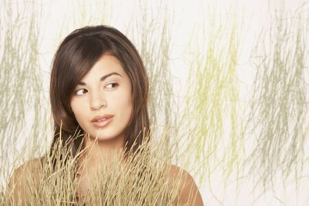 mischievious: Asian woman next to decorative grasses