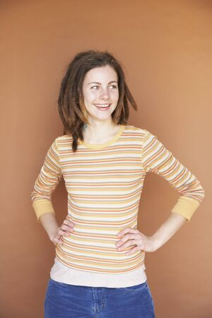 Young woman with dreadlocks and hands on hips Stock Photo