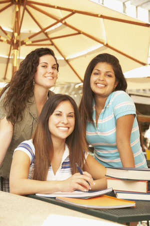 Three Hispanic women at cafe table with school books Stock Photo - 16092579