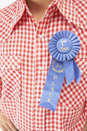 attired: Close up of blue ribbon on man's shirt