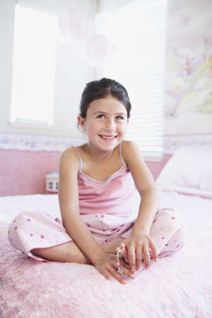 Hispanic girl sitting on bed Stock Photo - 16070639