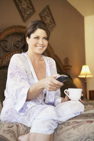 Woman holding coffee mug and watching television on bed Stock Photo - 16092598