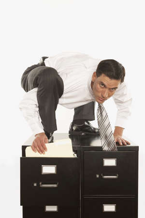 contortionist: Businessman filing on top of filing cabinet