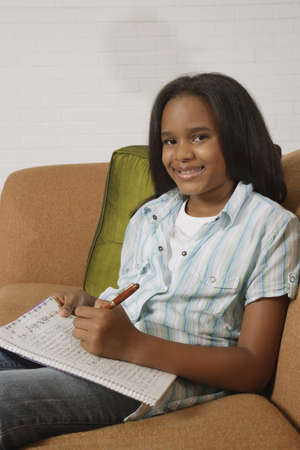African girl writing in notebook on sofa Stock Photo - 16092617