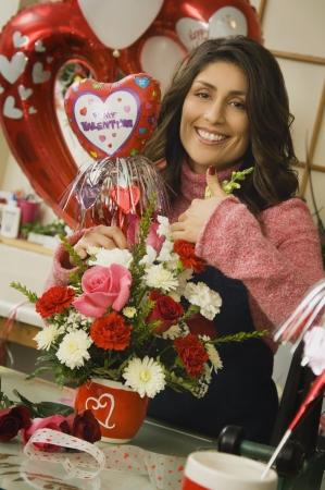 Hispanic female florist making Valentine's Day arrangement