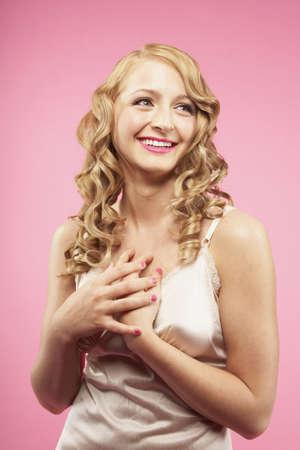 relishing: Studio shot of woman with hands over heart