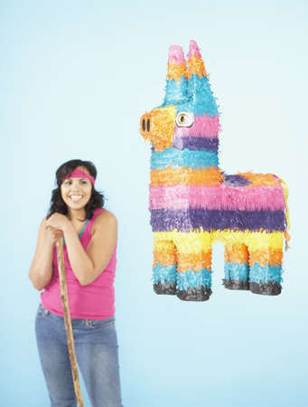 pinata: Hispanic woman standing next to pinata