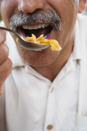 lower section view: Close up of middle-aged man eating