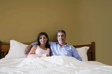 bedcover: Middle-aged couple sitting in bed