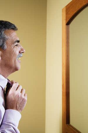 Middle-aged Hispanic man adjusting necktie Imagens