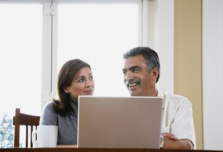 mischeif: Middle-aged couple using laptop