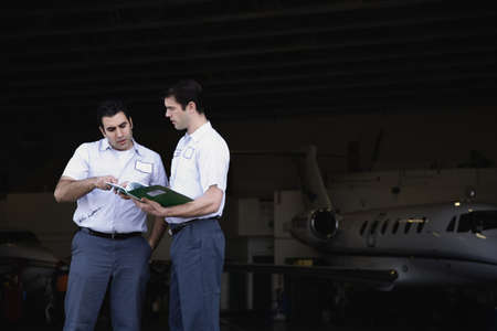 Two repairmen looking at paperwork in airplane hangar Stock Photo - 16092673
