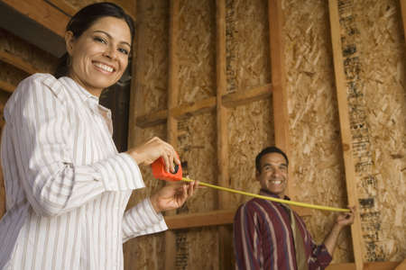 truelove: Hispanic couple using tape measure in construction site LANG_EVOIMAGES
