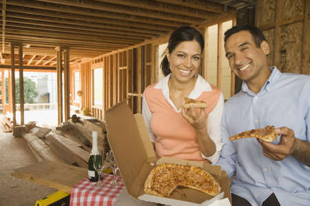 italian ethnicity: Hispanic couple having pizza and champagne at construction site LANG_EVOIMAGES