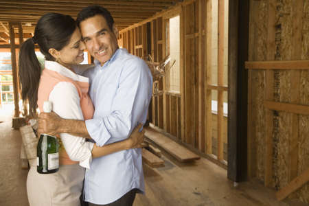 Hispanic couple hugging with champagne at construction site Stock Photo - 16092705