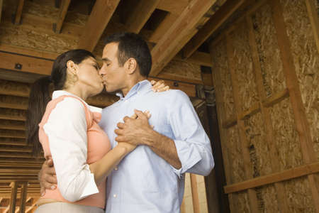 kisser: Hispanic couple kissing at construction site