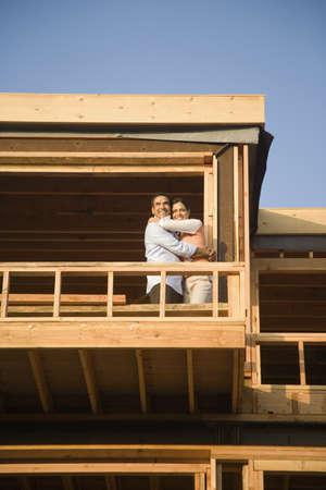 Hispanic couple hugging on balcony at construction site Stock Photo - 16092707