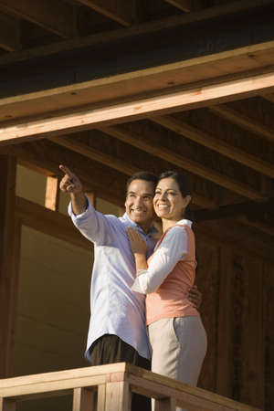 Hispanic couple pointing on balcony at construction site Stock Photo - 16092708