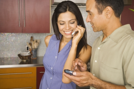electronic organizer: Hispanic couple using cell phone and electronic organizer LANG_EVOIMAGES