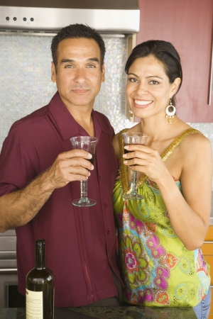 Portrait of Hispanic couple holding wine in kitchen Stock Photo - 16092720