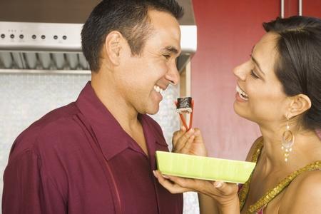 Hispanic couple eating sushi in kitchen Stock Photo - 16092721